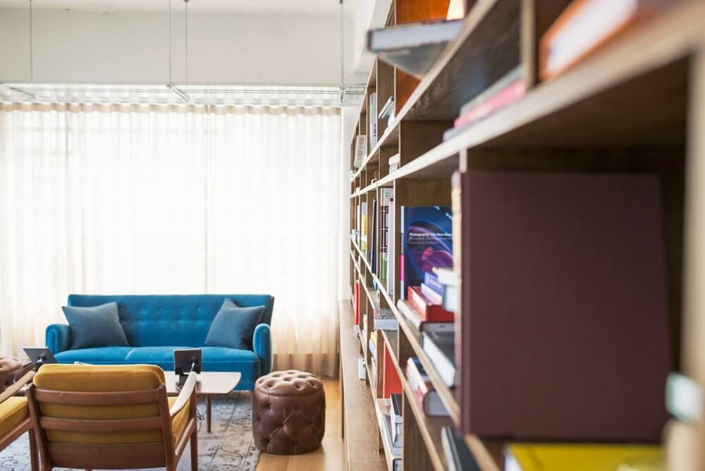 A long bookcase in a room with a sofa, a chair and a pouffe